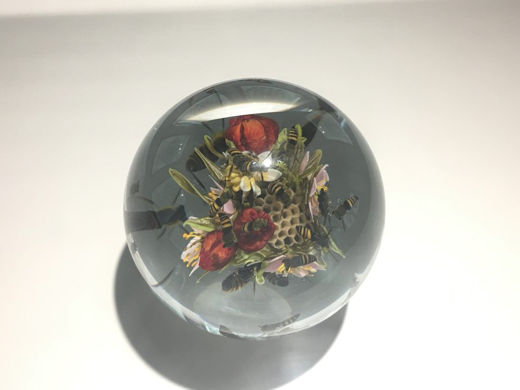 Spherical glass paperweight with a honeycomb, flowers, and honey bees suspended inside.